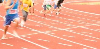 跑在轨道,模糊的运动的一个小组男性运动员 免版税图库摄影