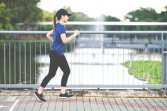 跑在边路方式的年轻可爱的亚裔赛跑者妇女在公开自然城市公园用湖水 免版税图库摄影