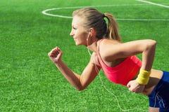 跑在运动服的体育场内的连续女孩 库存照片
