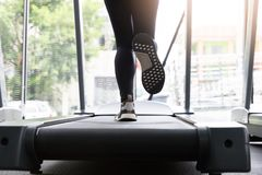 跑在连续机器的健身妇女在健身房,心脏的油脂烧 免版税库存图片