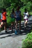 跑在道路的十几岁的女孩 免版税库存照片
