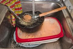 跑在金属水槽的肮脏的盘的水 库存照片