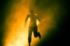 跑在雨中的被弄脏的人到黄灯 免版税库存照片