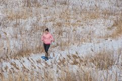 跑在雪的妇女在一个冷的春日 库存图片