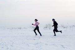 跑在雪的男人和妇女 免版税库存图片