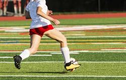 跑在领域下的女性高中足球运动员 免版税库存图片