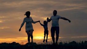 跑在领域的愉快的家庭在日落 一个家庭的剪影在一个夏天晚上 家庭爱的概念  影视素材