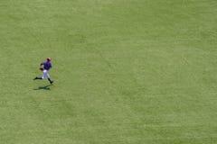 跑在领域的美国青年棒球运动员 图库摄影