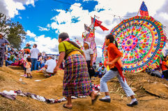 跑在风筝,万圣节,危地马拉前面的妇女 免版税库存图片