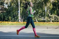 跑在马拉松期间的女运动员 库存照片