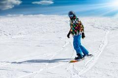 跑在高山山的倾斜下的年轻人挡雪板 冬季体育和休闲,休闲室外活动 蓝色 免版税库存照片