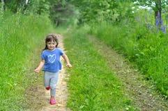 跑在晴朗的开花的森林里的小女孩哄骗戏剧户外 家庭的夏天乐趣有孩子 免版税库存图片