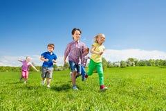 跑在绿色公园的愉快的小组孩子 免版税库存照片