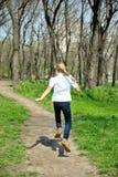 跑在绿色公园的年轻愉快的女孩 免版税库存照片