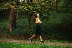跑在绿色公园,健康生活方式背景的妇女 免版税库存图片