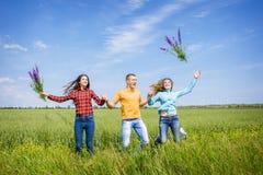 跑在绿色麦田的年轻愉快的朋友 免版税图库摄影