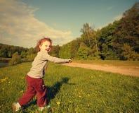 跑在绿草的愉快的微笑的孩子女孩 免版税图库摄影