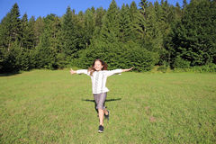 跑在绿草领域的小女孩 免版税库存图片