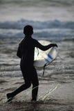 跑在conish的男孩与冲浪板 免版税库存照片