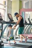 跑在spacy健身房的跑马场的年轻父亲与小儿子 免版税图库摄影
