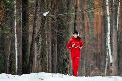 跑多雪的杉木森林的耳机的女孩 图库摄影