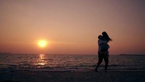 跑女孩的剪影供以人员在海海滩慢动作 股票录像
