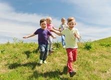跑小组愉快的孩子户外 免版税库存图片