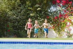 跑往游泳池的孩子 免版税库存图片
