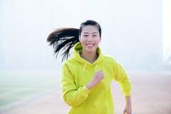 跑往照相机的一个美丽的女运动员的正面图 库存图片