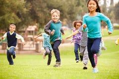 跑往照相机的小组幼儿在公园 免版税库存照片
