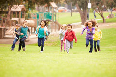 跑往照相机的小组幼儿在公园 图库摄影