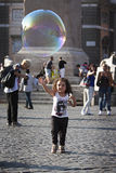 跑往肥皂泡的愉快的儿童女孩 免版税库存照片