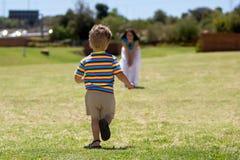 跑往他的孩子是母亲。 库存图片
