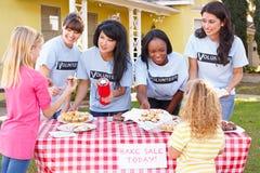 跑慈善的妇女和孩子烘烤销售 免版税库存照片