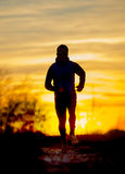跑户外在路与秋天太阳的足迹轨道的年轻体育人剪影正面图在橙色天空日落 免版税库存照片