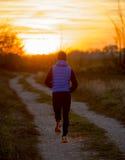 跑户外在路往秋天太阳的足迹轨道的后面观点的年轻体育人在与橙色天空的日落 库存照片