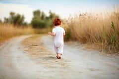 跑掉沿道路的逗人喜爱的小孩男婴在夏天领域 库存照片