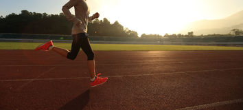 跑早晨在体育场轨道的晴朗的妇女 免版税库存图片