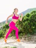 跑本质上的健身妇女 山的运动的亭亭玉立的女孩 库存照片