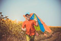 跑横跨与飞行在他的头的风筝的领域的男孩 免版税库存照片