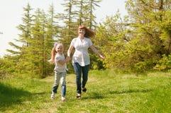 跑横跨草甸的母亲和女儿 免版税库存图片