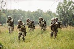 跑横跨领域和射击的小组战士 免版税库存照片