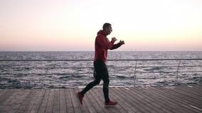 跑步一位年轻的运动员的侧视图英尺长度,做准备在拳击的主要训练前 近清早锻炼 股票视频