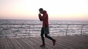 跑步一位年轻的运动员的迁徙的侧视图英尺长度,做准备在拳击的主要训练前 在美丽的鸟云彩之上颜色及早飞行金子早晨本质宜人的平静的反映上升海运一些星期日 股票录像