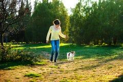 跑步与她的杰克罗素狗狗的愉快的少妇 免版税库存图片