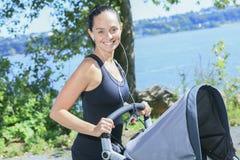 跑步与婴孩车的年轻母亲 库存图片