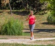 跑步和听到音乐的年轻白肤金发的妇女在公园 免版税库存照片