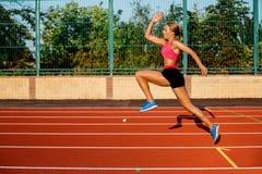 跑步和跑在体育场的运动轨道的侧视图美好的少妇锻炼 免版税库存照片