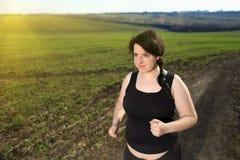跑步在乡下的超重妇女 库存图片