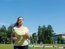 跑步在体育场的少妇 免版税图库摄影
